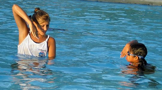 Swim instructor with young student