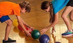 A young boy and girl reaching for dodgeballs